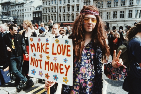 A man dressed as a hippy with a placard reading 'Make Love Not Money' at a Reclaim The Streets demonstration in London, 1st May 2000. (Photo by Steve Eason/Hulton Archive/Getty Images)